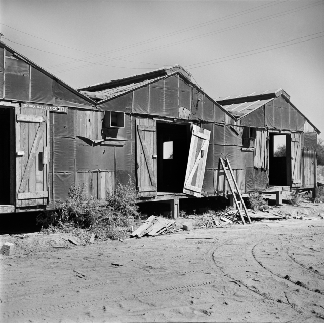 "Decaying barracks at the Poston Relocation Center in Arizona several months after the departure of the ""evacuees."" Hikaru Iwasaki 1945"