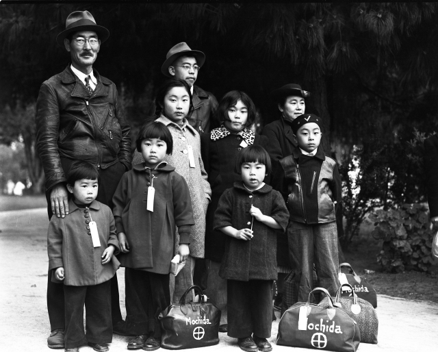 "Members of the Mochida family wait in Hayward, California, for their ""evacuation"" bus. Each wears an ID tag. The family operated a nursery and five greenhouses in Hayward. Dorothea Lange May 8, 1942"